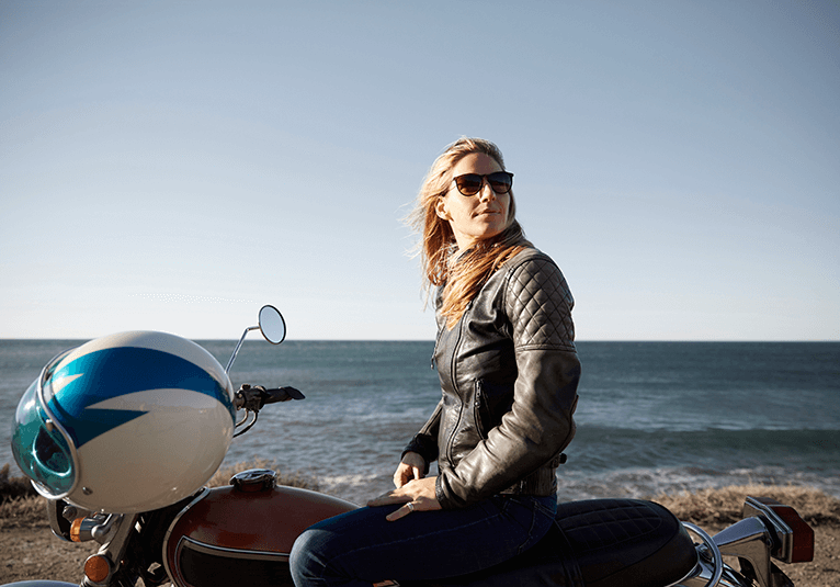 A woman in motorcycle leathers sitting on top of a motorcycle parked on a beach.